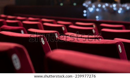 Empty theater with red chairs. Rear view. - stock photo