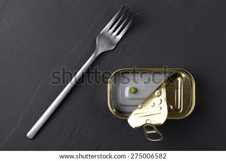 empty tin can on black stone background, food concept - stock photo