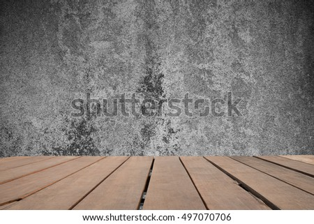 Empty top of brown wooden shelves on cement wall