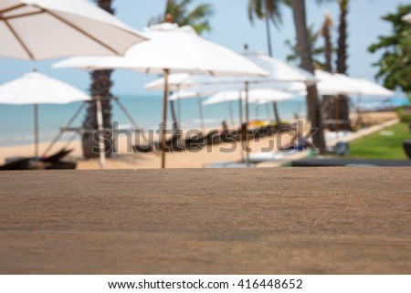 Empty top of wooden table and view of tropical beach background. - stock photo