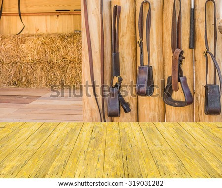 Empty top surface old yellow wooden table and riding horse equipment hang on wooden fence - stock photo