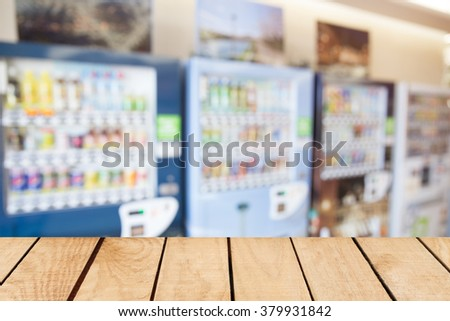 Empty top wooden table and blurred image of vending machine - stock photo