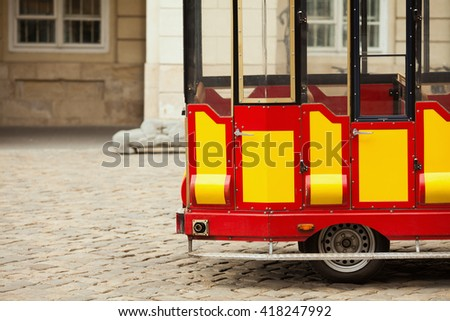 Empty tourist bus waiting for passengers on cobblestone paved road in European city. Copy-space. Outdoor shot - stock photo