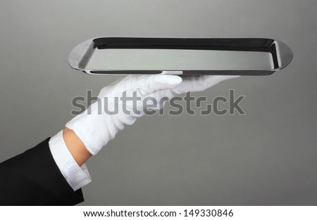 Empty tray in hand waiter on grey background - stock photo
