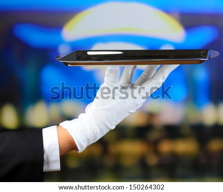 Empty tray in hand waiter on restaurant background - stock photo