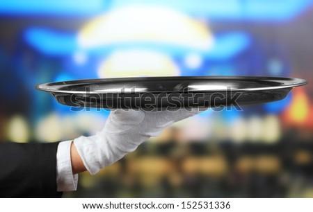 Empty tray in hand waiter on restaurant background - stock photo