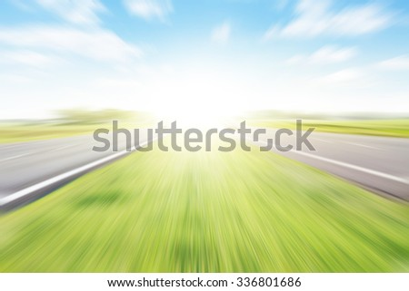 Empty two-lane highway in motion blur and sunlight. - stock photo