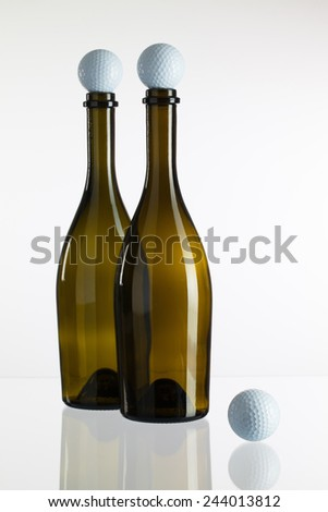 Empty two wine bottles and golf balls on a glass desk - stock photo