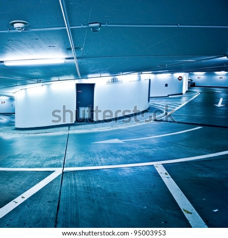 Empty underground parking lot area with interior in blue tones - stock photo