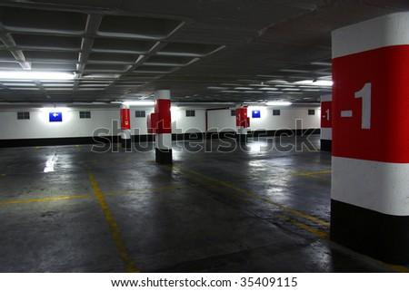 Empty underground parking lot with big concrete columns - stock photo