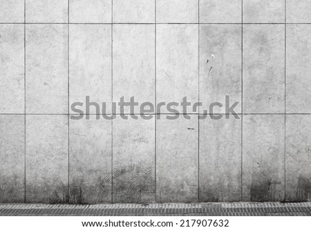 Empty urban interior with tiling on gray concrete wall and asphalt pavement - stock photo