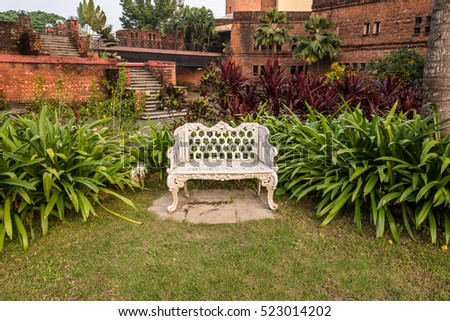Empty vintage garden chair in a resort garden waiting for someone to sit and relax.