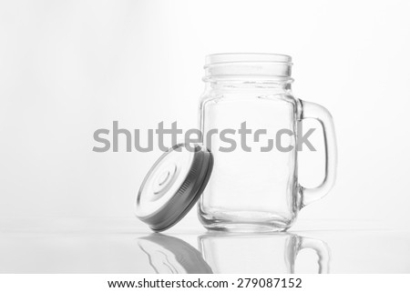 Empty vintage mason Jar  having lid and handle with on White background with reflection and copy space - stock photo