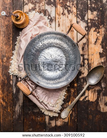 empty vintage pan with spoon on rustic wooden background, top view - stock photo