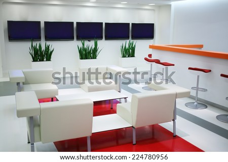 Empty waiting area with white chairs and plasma screens in office  - stock photo