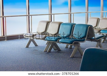 empty waiting chair on blue sky background - stock photo