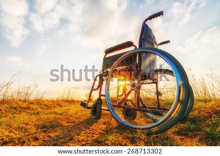 Empty wheelchair on the meadow at sunset. Miracle concept. Healed person raised and went away - stock photo