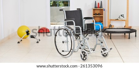 Empty wheelchair standing as symbol for physiotherapy in gym room - stock photo