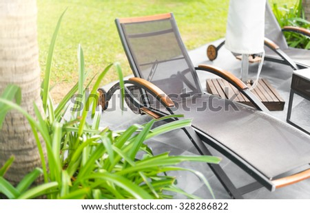 Empty wheeled chaise lounges on tiled floor outdoor in hotel area. Green plant and palm tree in foreground. Relaxation and sunbathing on hot day. Summer holidays and vacation on tropical resorts. - stock photo