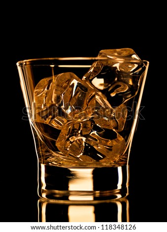 Empty whiskey glass with ice cubes on black background