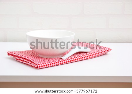 Empty white bowl and spoon on red tablecloth over table with brick wallpaper background - stock photo