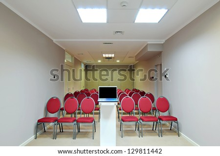 Empty white conference room with red armchairs - stock photo