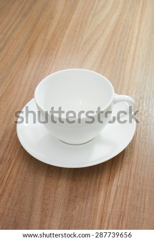 Empty white cup on wood background - stock photo