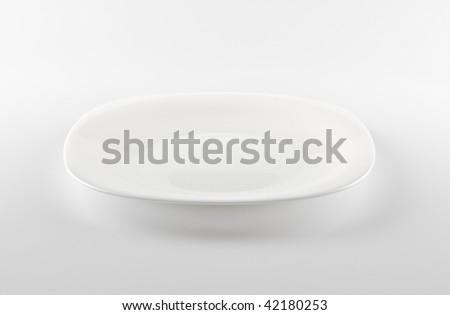 empty white dish on grey background - stock photo