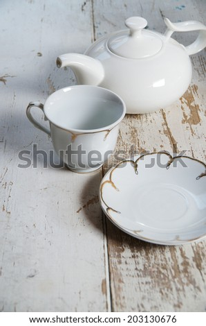 Empty white dishware on a wooden table. Cup, teapot, saucer - stock photo