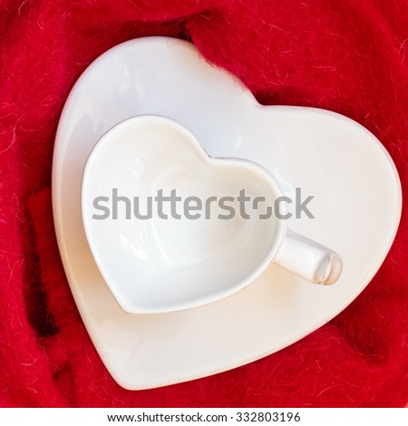 Empty white heart shaped coffe or tea cup and saucer on red cloth background. Top view - stock photo