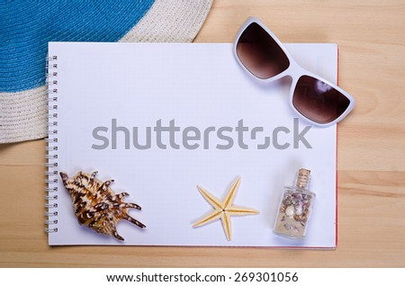 empty white notebook on wooden table surface with beach hat, seashells, starfish, sunglasses