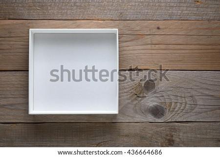 Empty white open box on wooden background - stock photo