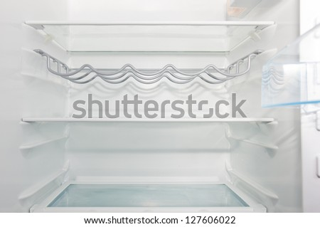 empty white  open fridge with some shelves