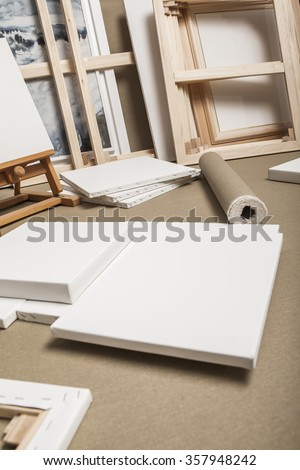 Empty white painter canvases and canvas roll and easel - painters program - stock photo