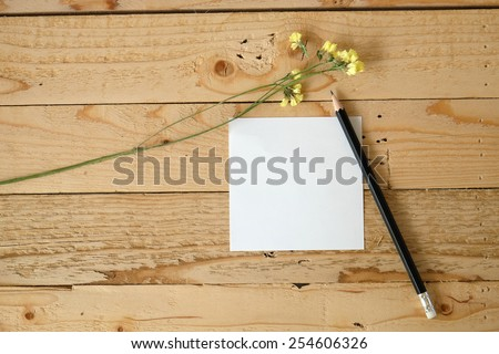 empty white paper note and pencil with yellow flowers on wooden table. - stock photo