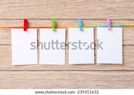 empty white photo frames hanging with clothespins on wooden background