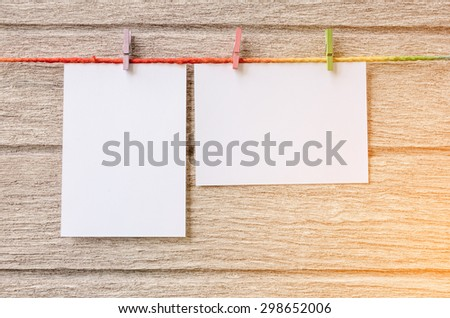 empty white photo frames hanging with clothespins on wooden background in vintage tone - stock photo