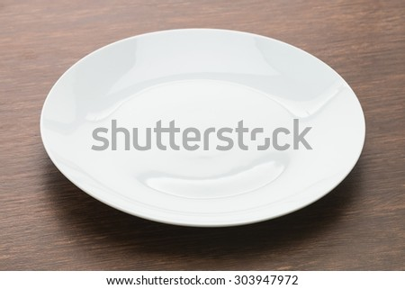 Empty white plate dish on wooden background - stock photo