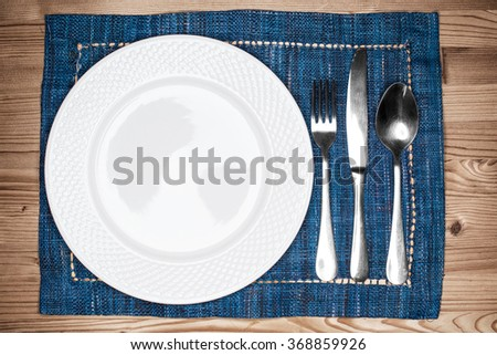 Empty white plate, fork, knife and spoon  on blue placemat over a wooden table - stock photo