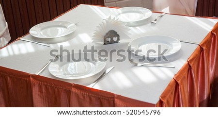 Empty white plate in a formal table setting on a table set with a white tablecloth