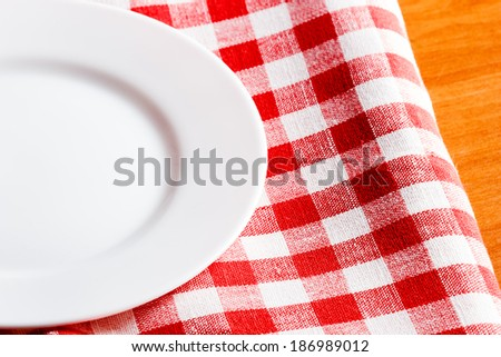 empty white plate on a red and white tablecloth - stock photo