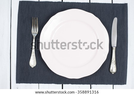Empty White Plate on black placemats and white wood with silverware