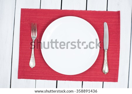 Empty White Plate on black placemats and white wood with silverware - stock photo
