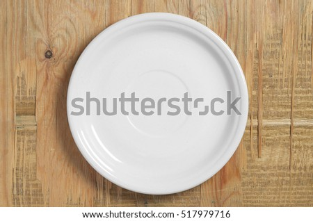 Empty white plate on old wooden background, top view
