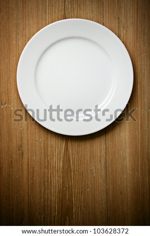 Empty white plate on wooden table - stock photo