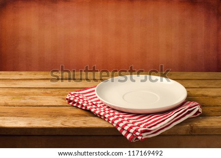 Empty white plate on wooden table over red grunge background - stock photo
