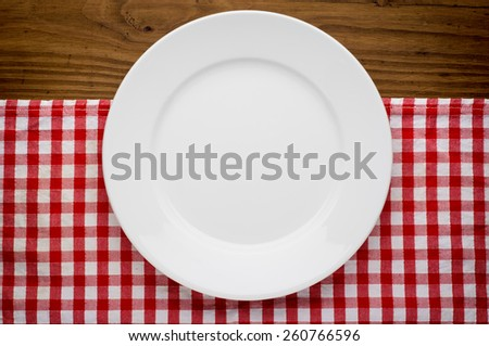 Empty white plate on wooden table over red grunge background