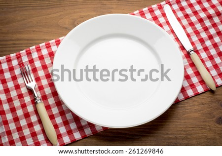 Empty white plate on wooden table over red grunge background with  fork and knife