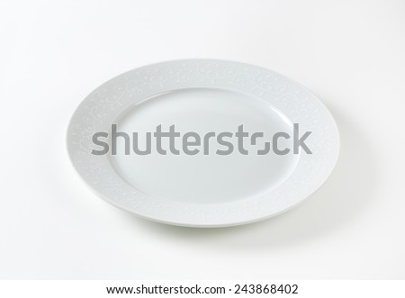 empty white plate with floral decoration on white background