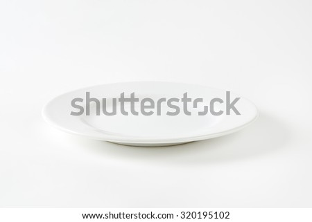 Empty white porcelain dinner plate with rolled edge - stock photo